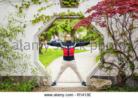 Retrato de un sonriente hombre de pie contra plantas Imagen De Stock