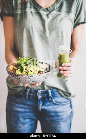 Almuerzo o cena saludable. Mujer en camiseta y pantalones vaqueros y permanente la celebración de la superbowl vegano o Buda bowl con hummus, ensaladas frescas, verduras, frijoles, co Imagen De Stock