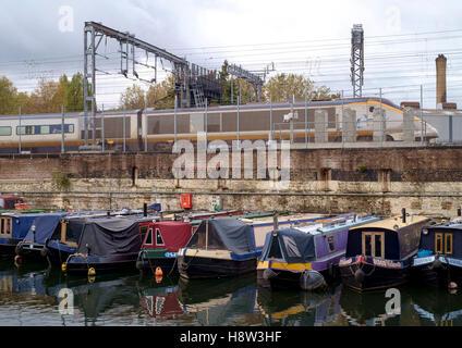 El Regents Canal en St Pancras en Londres. Un tren Eurostar discurre junto a un canal, cuenca de amarrados narrowboats. Imagen De Stock