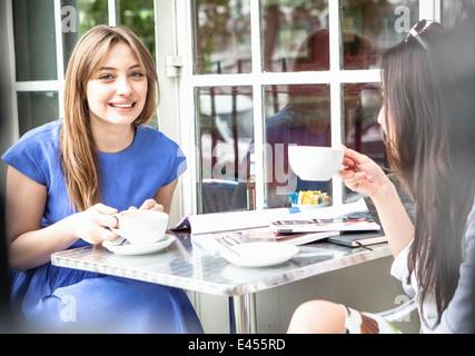 Dos mujeres jóvenes sentado fuera de la cafetería, bebiendo café Imagen De Stock