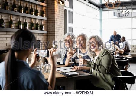 Las mujeres mayores amigos con vino posando para fotografía en restaurante. Imagen De Stock