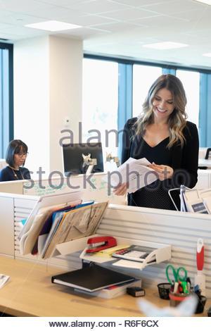 Clasificación trámites empresaria sonriendo en la oficina Imagen De Stock