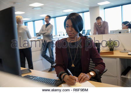La empresaria de tomar notas en equipo en armario de oficina Imagen De Stock
