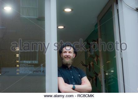 Barber inclinándose en portada de Barber shop Imagen De Stock