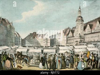 Una escena con mucho movimiento en la feria de Leipzig como molino de gente alrededor de los puestos. Imagen De Stock