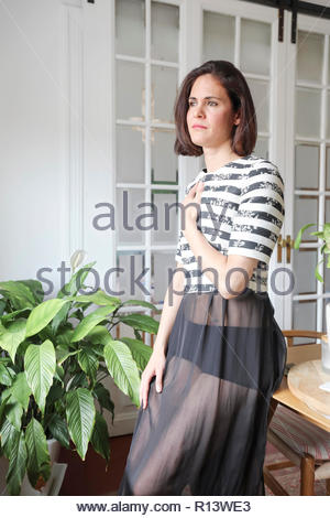 Una hermosa mujer de pie por plantas en macetas Imagen De Stock