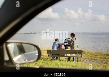 Los padres con hijos (18-23 meses) sentado en un banco por mar Imagen De Stock