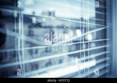 Hombre viejo mirando hacia afuera de la ventana a través de las persianas. Concepto de barrio de vigilancia Imagen De Stock