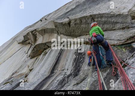 Las hembras jóvenes de escalador escalada cara, vista de ángulo bajo, el jefe, Squamish, British Columbia, Canadá Imagen De Stock