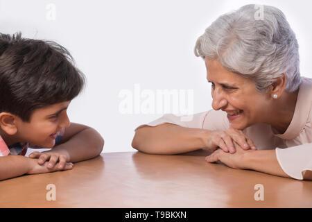 Abuela y nieto inclinarse sobre la mesa Imagen De Stock