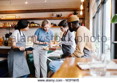 Administrador de servidores y hablar de la comida en el restaurante Imagen De Stock