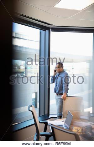 Empresario hablando por teléfono inteligente en la sala Imagen De Stock