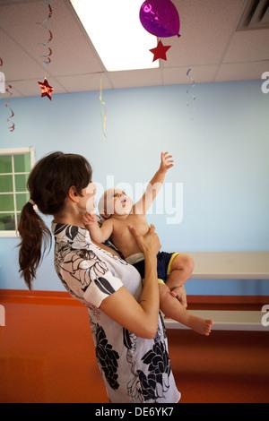 Llega hasta 10 meses para tratar de agarrar un globo mientras estuvo detenido por la madre. Imagen De Stock