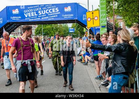Una mujer participante siendo recibido por sus amigos en la línea de meta durante el primer día.Ya que es el más grande del mundo multi-día caminando, el evento de cuatro días de marzo es visto como el primer ejemplo de deportividad y pegado internacional entre militares y civiles y de las mujeres de muchos países diferentes. Los participantes en la 103ª comenzaron los cuatro días marchas en Nijmegen, en la Wadren a las 4am, cruzaron el puente Waalbrug (la legendaria de Nijmegen), y pasando por la ciudad de Elst (el día), donde el color oficial era azul. El día era frío, con temperaturas inferiores Imagen De Stock