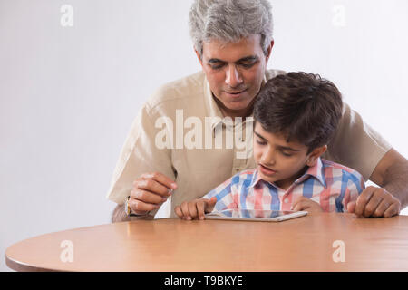 Abuelo y nieto sentados juntos utilizando tablet digital Imagen De Stock