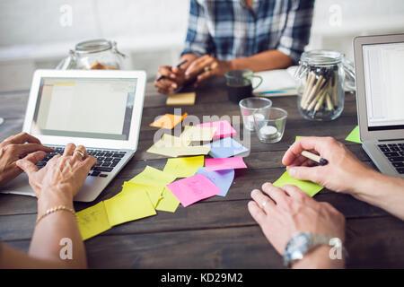 Tres compañeros que trabajan con ordenador portátil y post-it notes Imagen De Stock