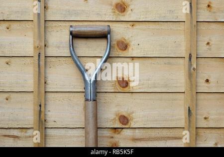 Empuñadura de pala inclinada contra el jardín vallado de madera de instrumentos Imagen De Stock