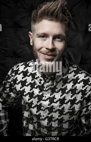 Retrato de estudio de un joven barbudo en una camiseta en blanco y negro. Imagen De Stock