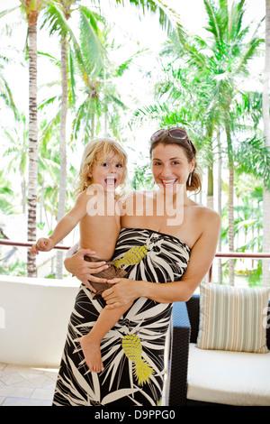 Muchacha elegante con el bebé cerca de palmeras Imagen De Stock