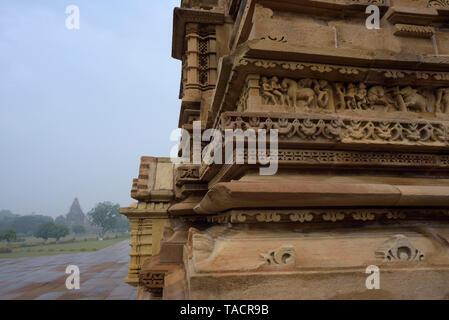 SSK - 473 bellamente y exquisitamente ordenados antiguo templo denominado Kandariya Mahadev dedicado al dios hindú Shiva El Señor con esculturas de surasundaris o bellezas celestiales y los dioses y goddessses y tallados en primer plano y en el fondo del templo Vishwanath Khajuraho, Madhya Pradesh, India Asia el 13 de diciembre de 2014 Imagen De Stock