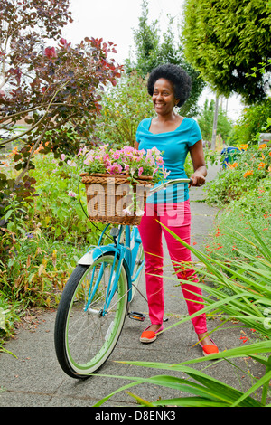 Mujer montando bicicleta retro con canasta de flores Imagen De Stock