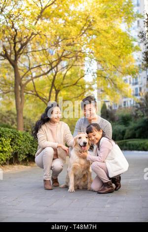 Una joven familia feliz jugando con perro Imagen De Stock