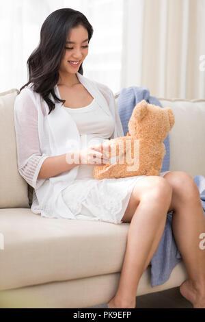 Alegre mujer embarazada jugando con osito de peluche Imagen De Stock