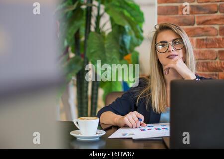 Una hermosa chica con gafas trabaja en un portátil fuera de la oficina. Comienzo de la jornada de trabajo con una taza de café. Negocio de ventas online Imagen De Stock