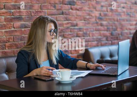 Hermosa joven mujer de negocios que trabaja para una taza de café. El concepto de trabajo activo. Adicta al trabajo. Imagen De Stock