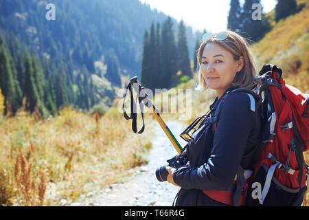 Retrato seguro joven fotógrafo de mochilero en sunny trail Imagen De Stock