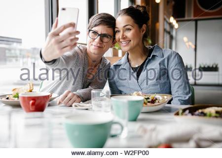 Feliz amigos tomando selfie en restaurante. Imagen De Stock
