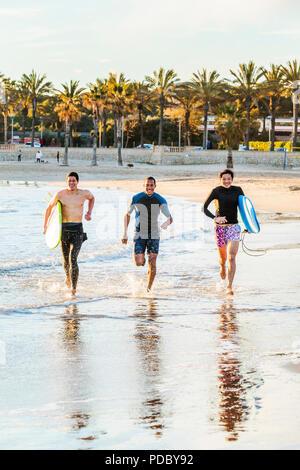 Entusiasta surfista masculino ejecuta en surf en la playa. Imagen De Stock