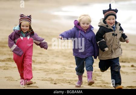 Fotografía de niños corriendo familia ejercicio playa vacaciones de invierno Imagen De Stock