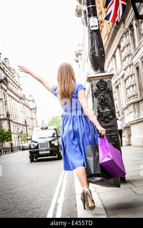 Mujer joven marcar hacia London taxi Imagen De Stock
