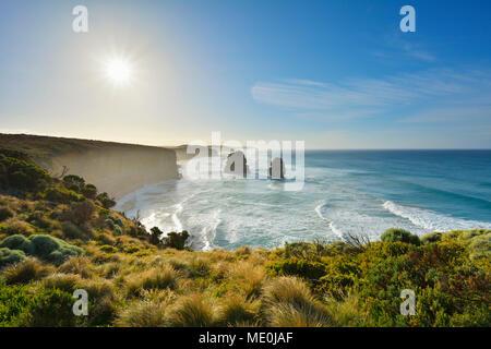 Las pilas de piedra caliza de los Doce Apóstoles retroiluminada por el sol a lo largo de la Great Ocean Road en Princeton en Victoria, Australia Imagen De Stock