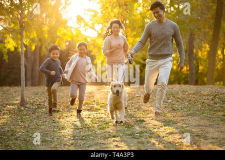 Feliz familia joven con perro en otoño woods Imagen De Stock