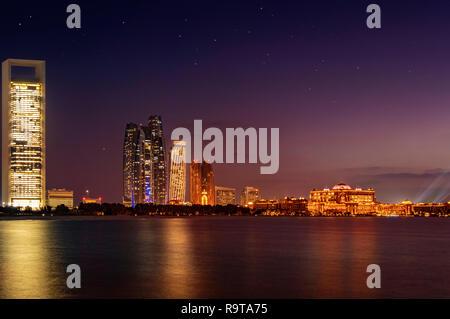 Hermosa foto de Abu Dhabi al anochecer. El fondo muestra la silueta de la ciudad con el palacio presidencial y Etihad towers. Imagen De Stock