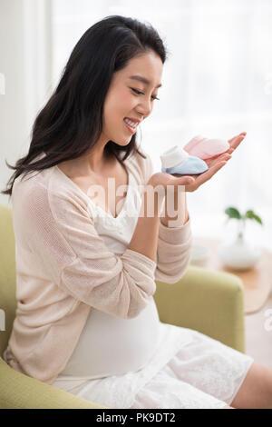 Mujer embarazada alegre celebración baby calcetines Imagen De Stock