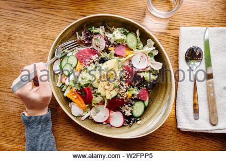 Perspectiva Personal mujer comer ensalada en restaurante. Imagen De Stock