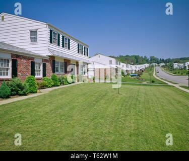 1970 SUBURBAN ladrillo y tablillas casa con césped de hierba verde fresca - KB9515 HAR001 HARS elegante soleado cielo azul segada tablillas HAR001 Old Fashioned persianas Imagen De Stock