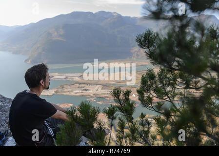 Escalador macho mirando sobre el lago del jefe, Squamish, British Columbia, Canadá Imagen De Stock