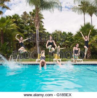 Varón y mujer multiplicados digitalmente saltando a la piscina Imagen De Stock