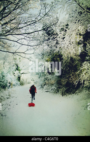 Chica corriendo en la nieve con trineos Imagen De Stock