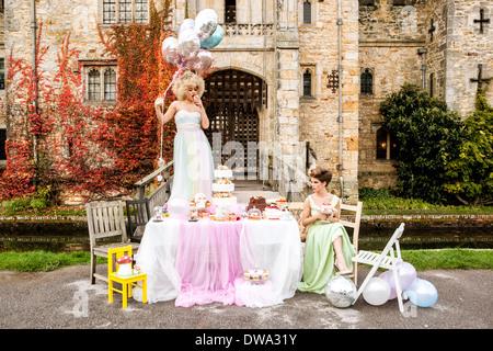 Novia de pie sobre la tabla, bridesmaid sentado Imagen De Stock