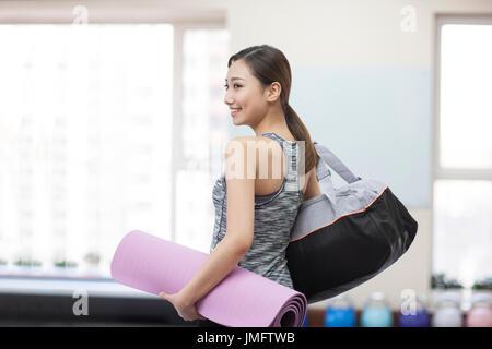 Mujer joven con esterilla de yoga en el gimnasio Imagen De Stock