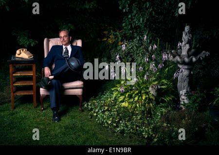 Un hombre vestido con un traje se sienta en una silla junto a un viejo estilo de teléfono rotativo en un exuberante y verde jardín. Imagen De Stock