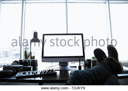 Perspectiva personal masculino fotógrafo con pies encima del escritorio Imagen De Stock