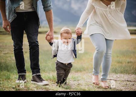 Los padres caminando con su hijo en el campo Imagen De Stock