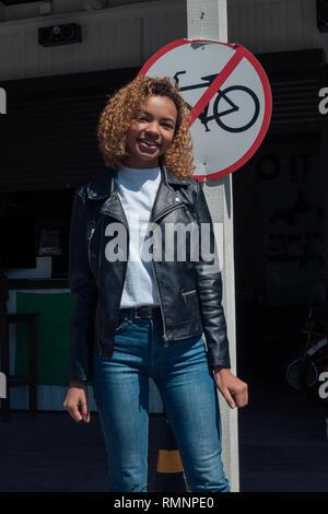 Hermosa muchacha africana permanente sonriente posando cerca del aparcamiento de bicicletas Imagen De Stock