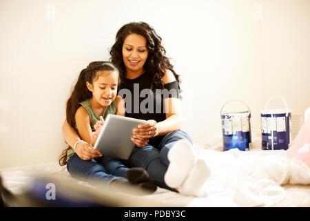 Madre e hija con tableta digital la preparación de proyecto de pintura Imagen De Stock